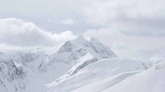 view of snow capped mountains on a cloudy winter day - snow stock videos & royalty-free footage