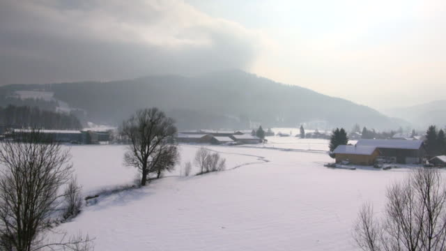 WS AERIAL View of snow covered fields in winter / Kochel, Bavaria, Germany