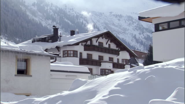 MS View of snow covered lodge with snowy mountains in background / Galtur, Tyrol, Austria