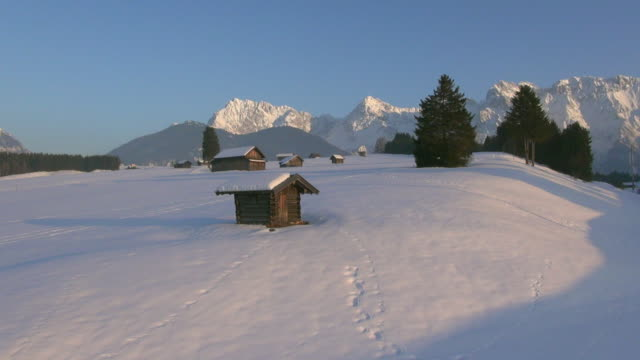 ws aerial view of snow covered meadows with traditional hay barns and mountains karwendel in winter / wallgau, bavaria, germany - karwendel mountains stock videos and b-roll footage