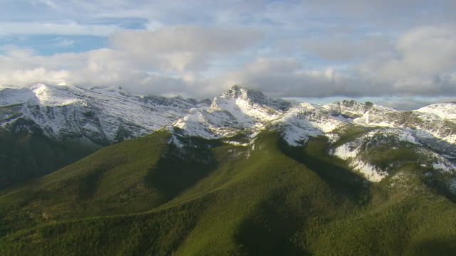 ws aerial zi view of snow covered weather peak in mission mountains / st. ignatius, montana, united states - 気まぐれな空点の映像素材/bロール
