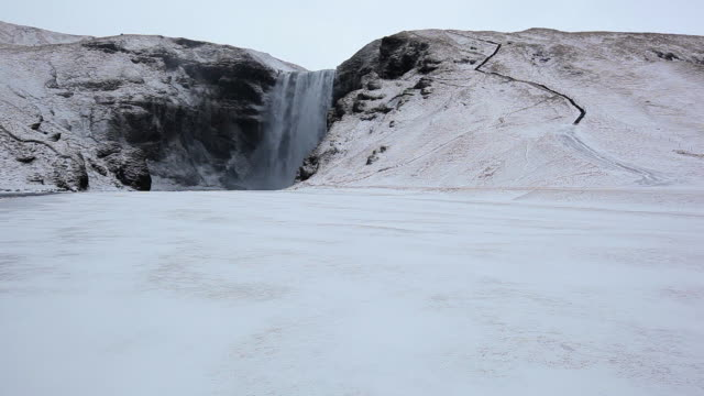 ws view of snow covers area around waterfall / iceland  - waterfall stock videos & royalty-free footage