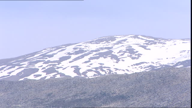 stockvideo's en b-roll-footage met view of snow-capped mount hermon which straddles the border between syria and lebanon and has the highest permanently manned un position in the world. - benen gespreid