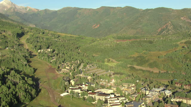 WS AERIAL View of snowmass winter resort village in valley surrounded by mountains / Aspen, Colorado, United States