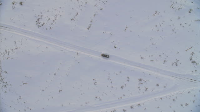 ws aerial view of snowplow driving on road / mammoth lakes, california, usa - mammoth lakes video stock e b–roll