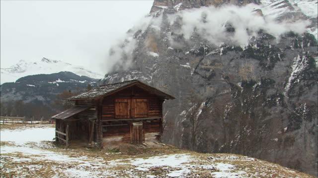 ws pan view of snowy mountain village in winter / gimmelwald, berner oberland, switzerland - berner alpen stock-videos und b-roll-filmmaterial