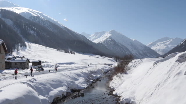 View of snowy mountains and mountain creek, distant skiers