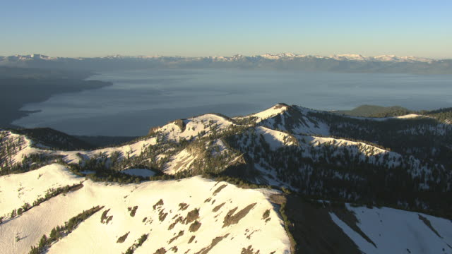 ws aerial view of snowy peaks with trees and lake tahoe in early morning / nevada, united states - californian sierra nevada stock videos & royalty-free footage