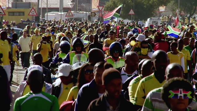 vidéos et rushes de ws slo mo view of soccer fans walking through street / johannesburg, gauteng, south africa - république d'afrique du sud