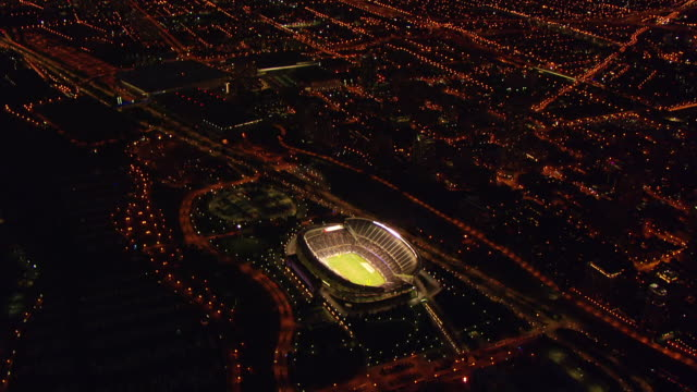 ws zi aerial pov view of soldier field stadium with downtown at night / chicago, cook county, illinois, united states  - アメリカンフットボール場点の映像素材/bロール