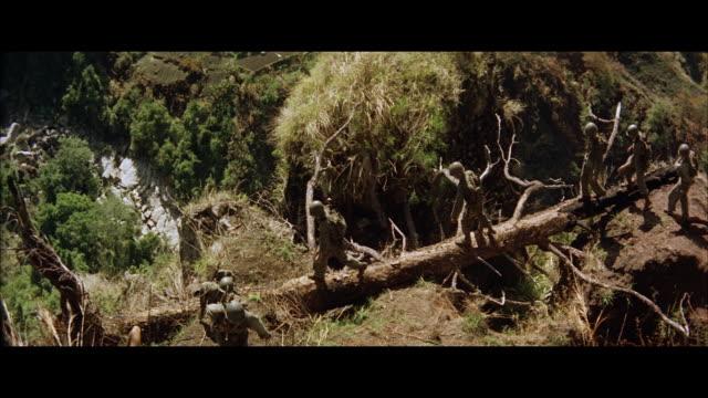 ws pan view of soldiers cross deep ravine on fallen log - ravine stock videos & royalty-free footage