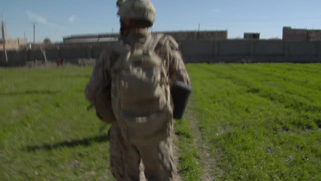 stockvideo's en b-roll-footage met view of soldiers walking through landscape / musa qala helmand province afghanistan - grind