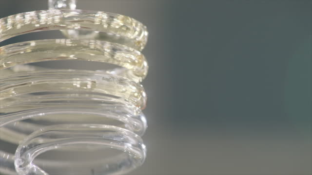 view of solution swirling in a spiral glass tube - spiral stock videos & royalty-free footage