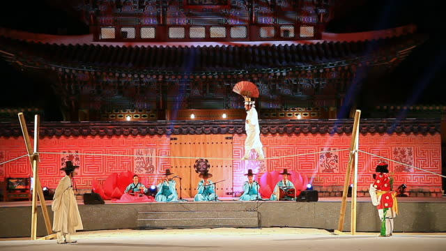 vídeos y material grabado en eventos de stock de ms view of some people performing tightrope walking with paper fan andothers playing korean traditional musical instruments against heungnyemun gate(traditional korean architecture) of kyongbokkung palace audio  / seoul, south korea - alambre