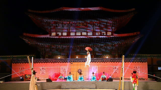 ms view of some people performing tightrope walking with paper fan andothers playing korean traditional musical instruments against heungnyemun gate(traditional korean architecture) of kyongbokkung palace audio / seoul, south korea - tightrope walking stock videos & royalty-free footage