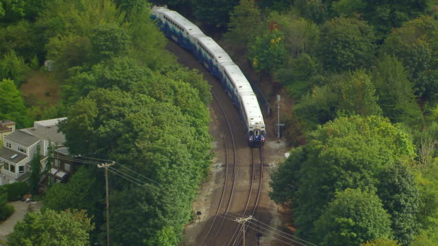 WS AERIAL ZI View of Sounder commuter rail train on curved tracks through trees / Seattle, Washington, United States