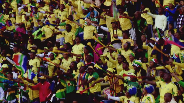 WS View of South African fans waving vuvuzela's at soccer match / Johannesburg, Gauteng, South Africa