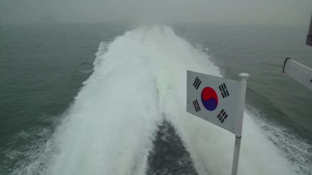view of south korean flag and water spray in ongjin-gun (natural habitat for endangered birds), incheon - south korean flag stock videos & royalty-free footage