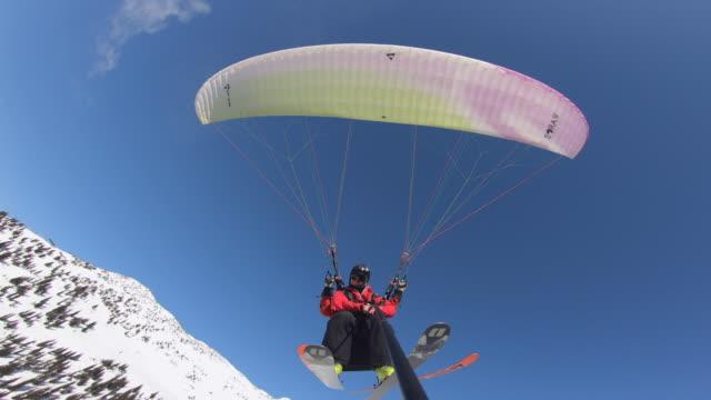 vidéos et rushes de pov view of speed flying riding parachuting paragliding, snow skiing down a mountain. - parapente