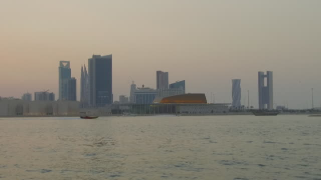 view of speedboats passing in front of the financial harbor district and the bahrain national museum and theatre complex at dusk. - ダウ船点の映像素材/bロール