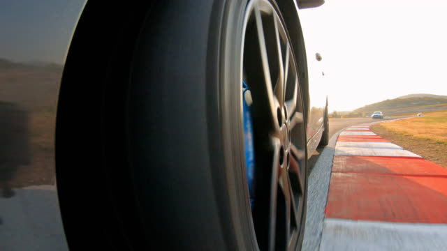view of sports car wheel spinning while in pursuit of competition during a motor sport event - pursuit sports competition format stock videos & royalty-free footage