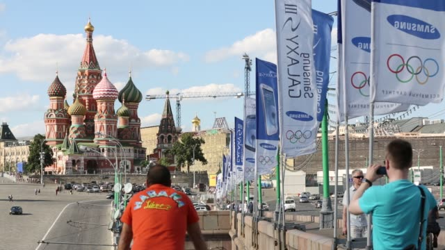 view of st basil's cathedral from a bridge / summer weather / tourists taking photos / flags waving with olympic rings advertising samsung view of... - 記号点の映像素材/bロール