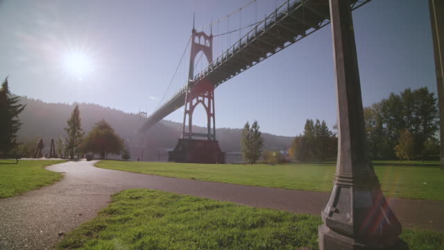 ws ds view of st. johns bridge large steel suspension bridge in gothic style, looms large over willamette river / portland, oregon, united states - portland oregon fall stock videos & royalty-free footage