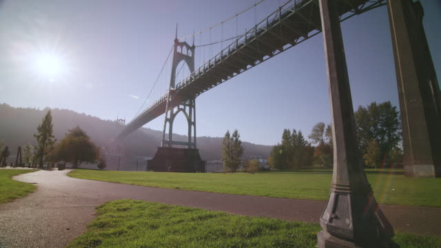 WS View of St. Johns Bridge large steel suspension bridge in Gothic style, looms large over Willamette River and park beneath it / Portland, Oregon, United States