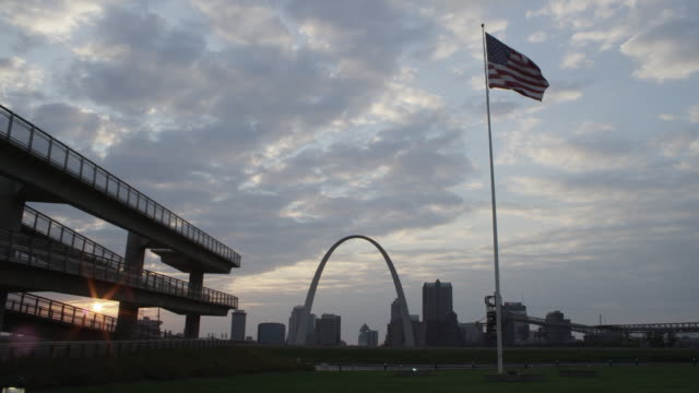 ws view of st. louis skyline and gateway arch with american flag at sunset / st. louis, missouri, united states - jefferson national expansion memorial park stock videos & royalty-free footage