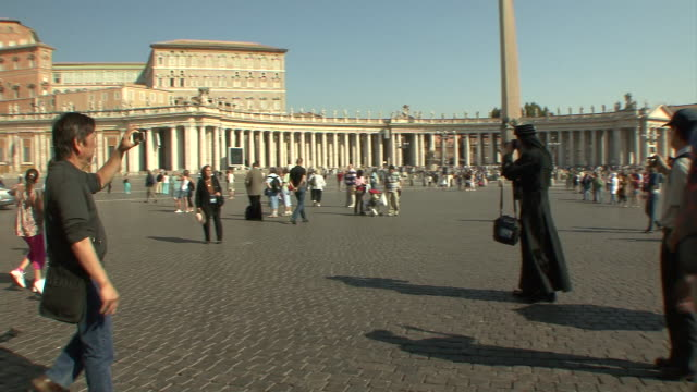ws pan zi tu view of st peter' square with tourists and orthodox priest photographing / rome, italy    - priester stock-videos und b-roll-filmmaterial