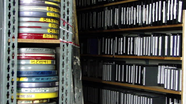 view of stacks of films in film cans on shelves with shelves full of folders on the right side in a film archive in san francisco, california on... - film reel stock videos & royalty-free footage