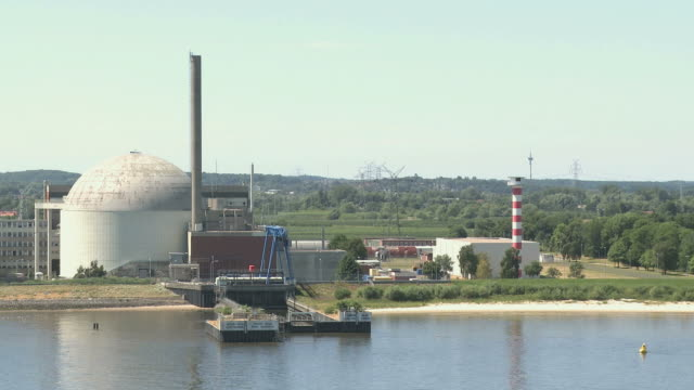 ws pan view of stade atomic power plant / river elbe, lower saxony, germany - nuclear power station stock videos & royalty-free footage
