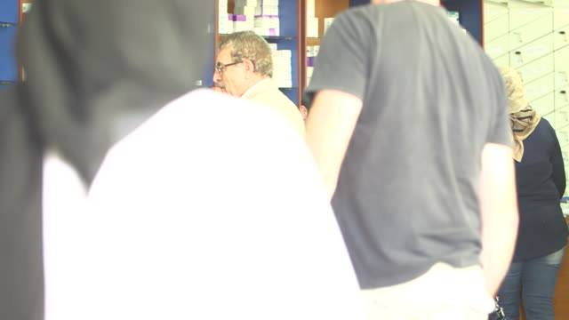 view of staff and emiratis, asians and caucasians inside a pharmacy. - prescription medicine stock videos & royalty-free footage