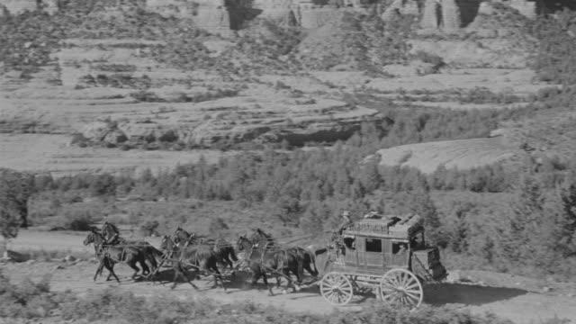 vidéos et rushes de ws ts view of stagecoach riding through desert through mountains - voiture hippomobile