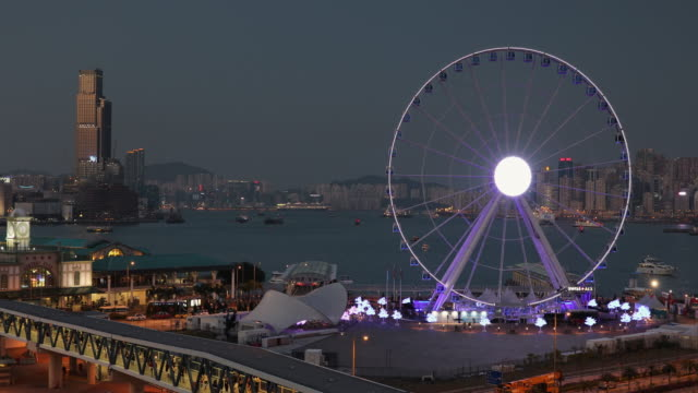 view of star ferry pier and ferris wheel at dusk, hong kong, china, asia - fähre stock-videos und b-roll-filmmaterial