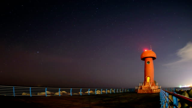 View of star field over lighthouse of Namaehang harbor at night