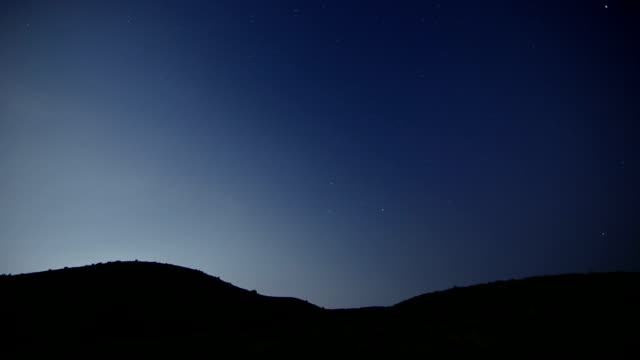 view of star trail over yongnunioreum (mountain hill) in jeju - horizont stock-videos und b-roll-filmmaterial