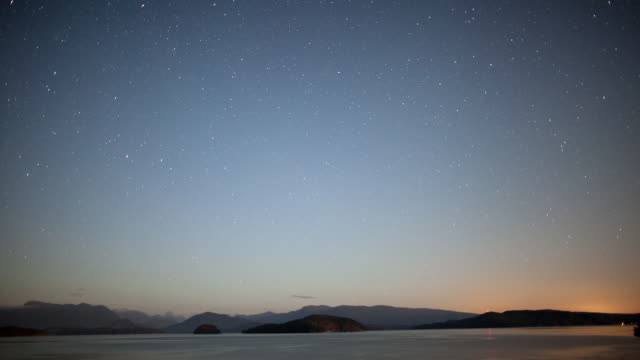 vídeos de stock, filmes e b-roll de ws t/l view of stars moving over island and strait of georgia with mountains / cortes, british columbia, canada   - o anoitecer