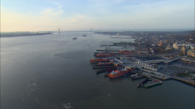 ws pov aerial view of staten island ferry terminal with verrazano narrows bridge in background / new york city, new york, usa - ferry terminal stock videos & royalty-free footage