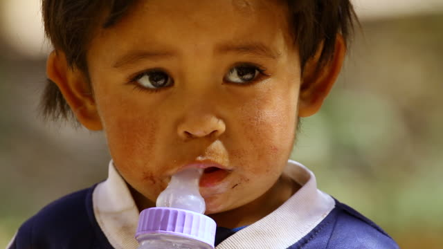 cu view of static little boy with baby milk bottle / angostura, chile - wiese stock videos & royalty-free footage
