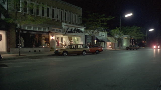 WS PAN View of station wagon passing by commercial street in small town