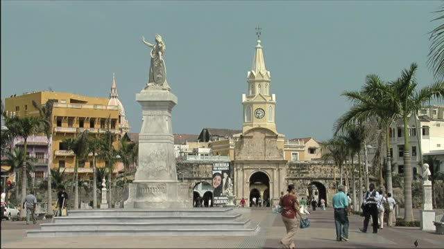 ws view of statue and people walking on street / colombia - clock tower stock videos and b-roll footage