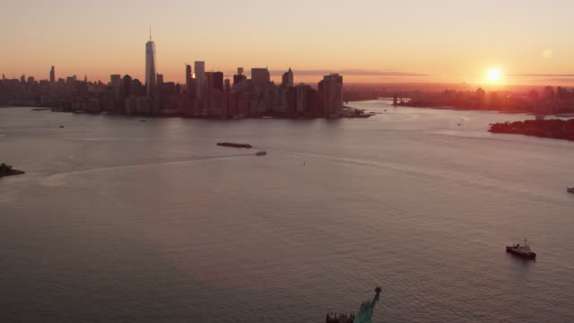 AERIAL MS View of statue liberty and city on a distance with rising sun / New York City