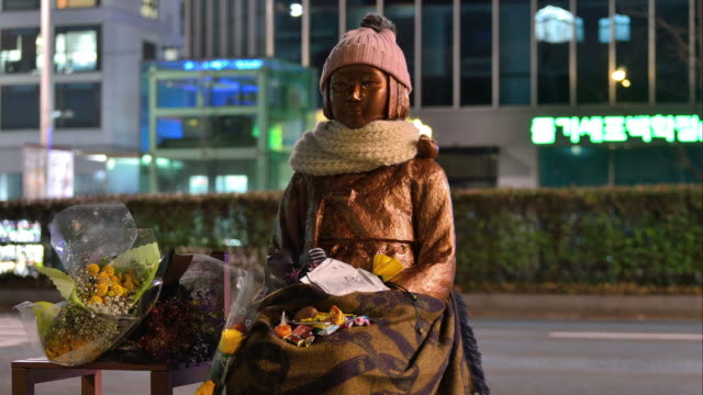 vidéos et rushes de view of statue of comfort woman (also known as statue of girl) at night - coréen