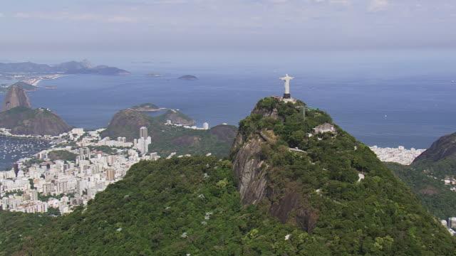 vídeos de stock, filmes e b-roll de ws aerial view of statue of cristo corcobado rio de janeiro with ocean / rio de janeiro, brazil - international landmark