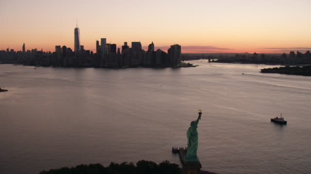 AERIAL MS view of statue of liberty and city on a distance at early morning / New York City
