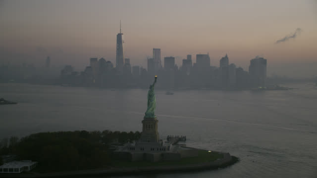 """""""WS ZO AERIAL View of Statue of liberty at sunrise with lower Manhattan in background / New York City, United States"""""""