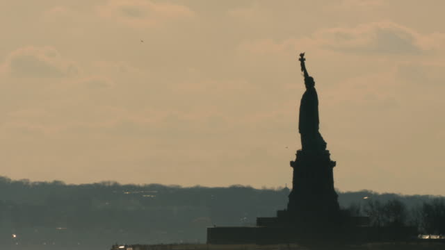 ws view of statue of liberty at sunset with ferry crossing / new york city, new york, usa  - フェリー船点の映像素材/bロール