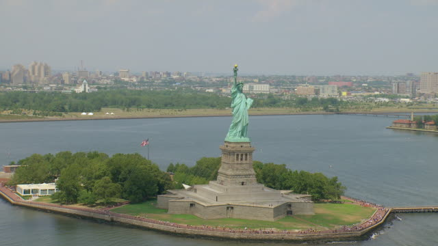 ws aerial view of statue of liberty on liberty island in front of  suburbs / new york, united states - 自由の女神点の映像素材/bロール