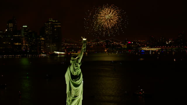 MS AERIAL View of statue of liberty with fireworks and yachts in hudson river at night / New York City